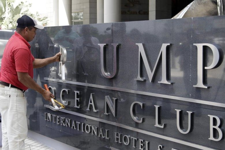 A worker removes the Trump lettering from the sign outside the Trump Hotel in Panama City on Monday after the majority owner of the luxury hotel evicted Trump company employees in a contract dispute.