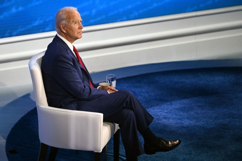 Biden, seated in a white chair on a blue carpeted stage, looks up and to his right.