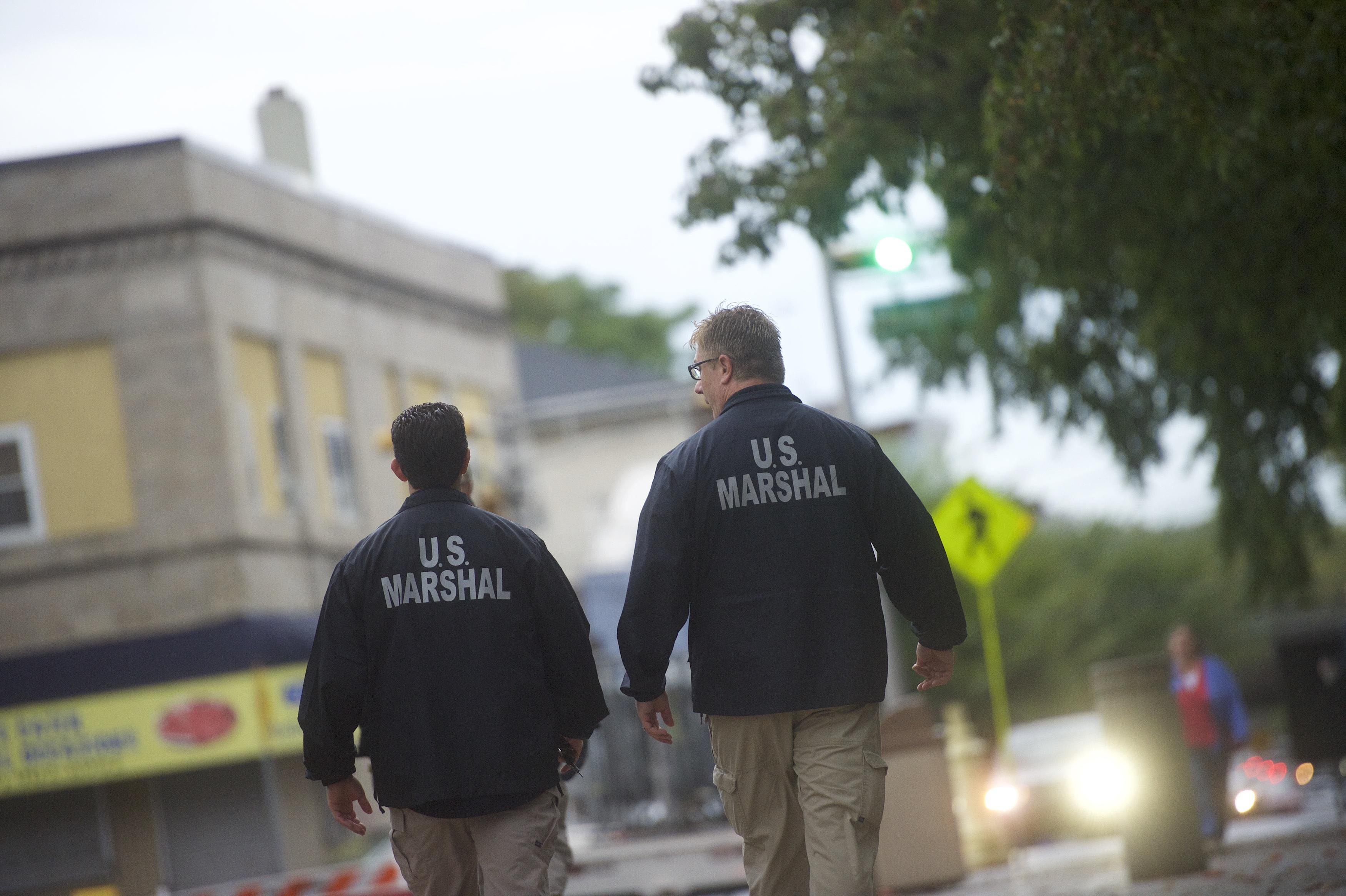 U.S. Marshals monitor activity outside a courthouse.