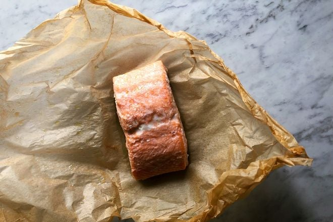 Piece of cooked salmon on brown wax paper on a marble countertop.