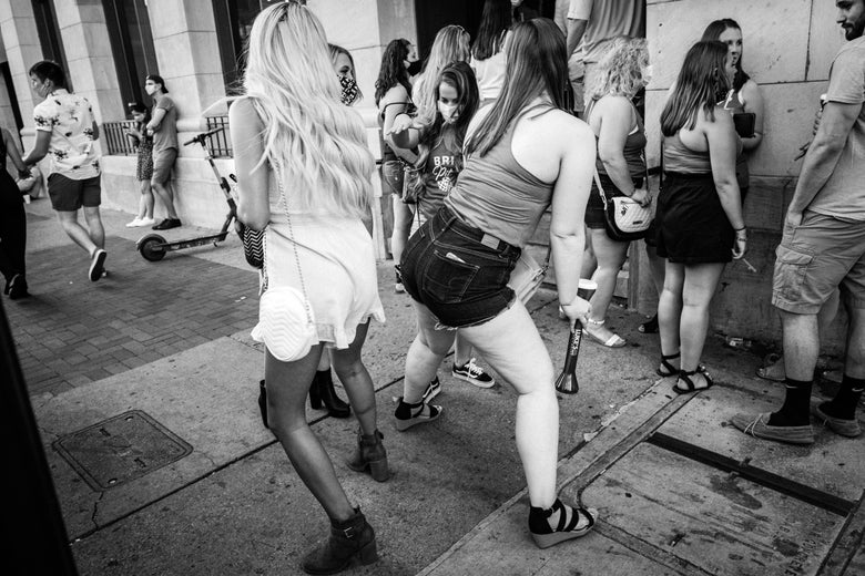 A black-and-white photo shows women holding drinks dancing together on the sidewalk.