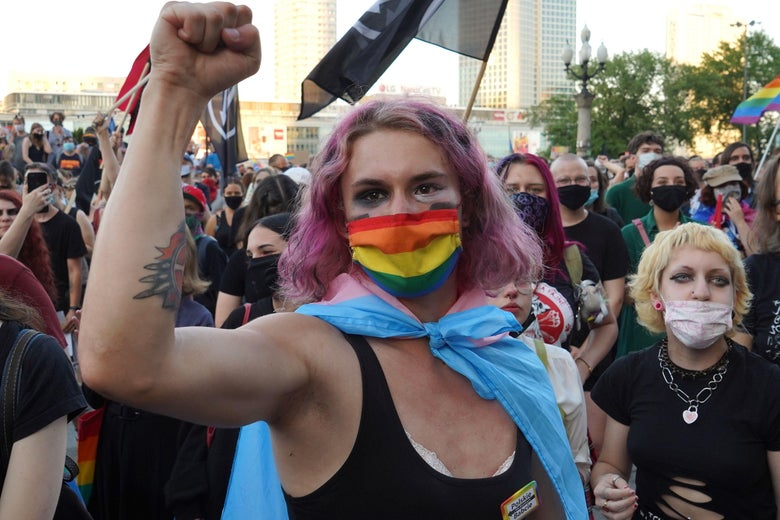 Activist with pink hair holds up her fist in front of a rainbow flag.