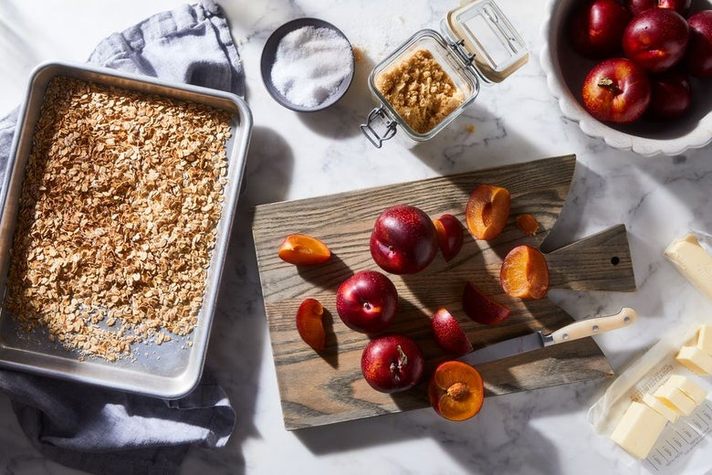 Apples, toasted oats, plums, sliced butter, brown sugar and salt on a counter top