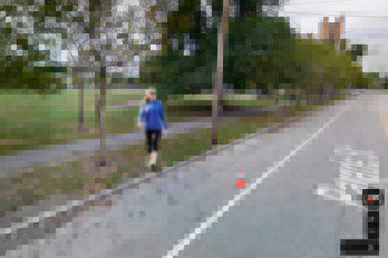 A pixelated screenshot of a Google Street View capture, of a street and sidewalk with a person walking next to some trees