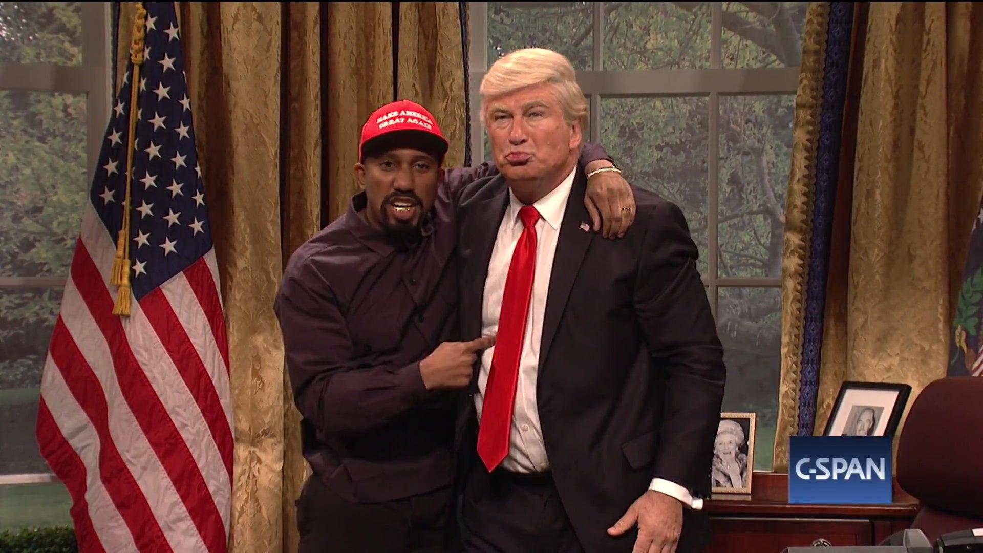 Chris Redd, dressed as Kanye West, embraces Alec Baldwin, dressed as Donald Trump.