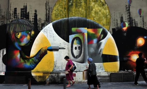People walk past graffiti in central Athens on June 17, 2013.