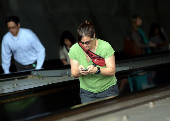 Woman checks her BlackBerry while riding an escalator in Washington, D.C.