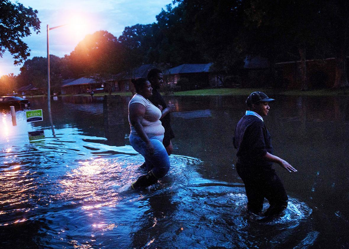 People walk through a flooded neighborhood August 15, 2016 in Baton Rouge, Louisiana.