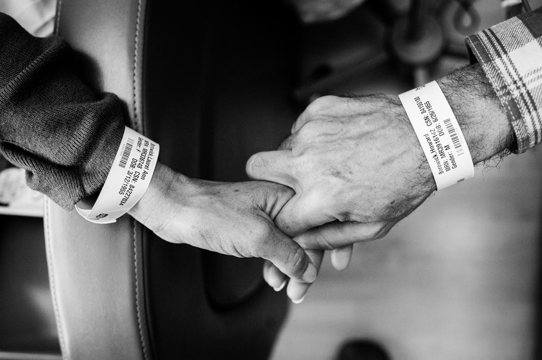 Like wedding rings, Laurel and Howie Borowick wear similar medical bracelets, which the nurses scan throughout their chemotherapy treatments together at the oncologists office. They do a dance, as both caretaker and patient and husband and wife, simultaneously trying to be there for the other but also trying to get through the day them selves. Greenwich, Connecticut. January, 2013.
