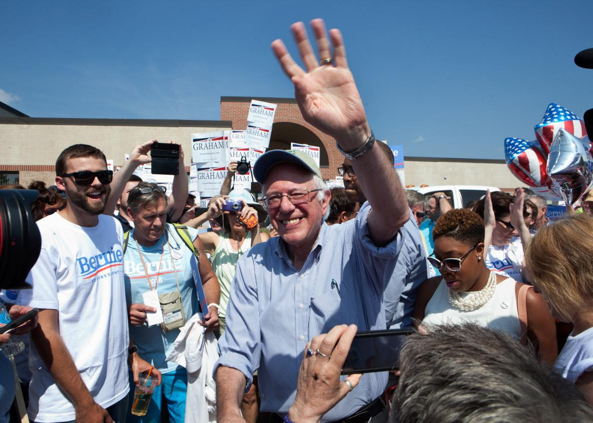 Bernie Sanders shakes hands with supporters at a rally