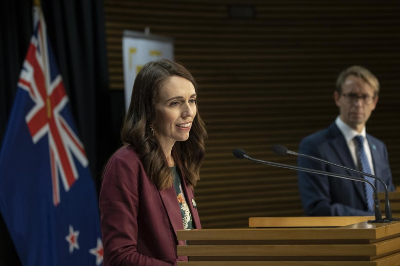 Jacinda Ardern speaks at a podium. Behind her is the New Zealand flag.