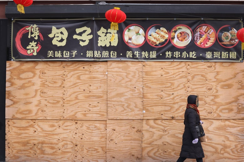 A person in a coat walks past a boarded-up restaurant.