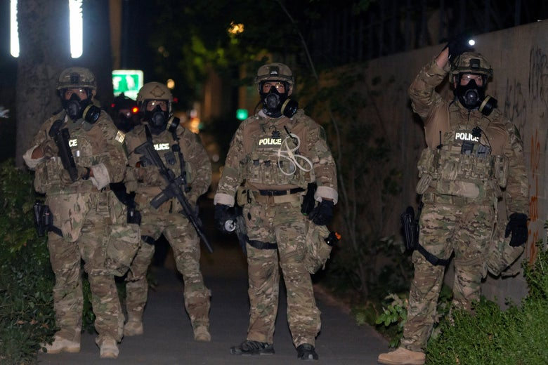 Four federal law enforcement officers wearing gas masks and full-body camo with the word POLICE emblazoned on the chest, at night. Two are holding guns.