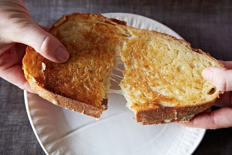 Two hands pull a grilled cheese sandwich apart. You can see strings of cheese stretch between the two sandwich halves.