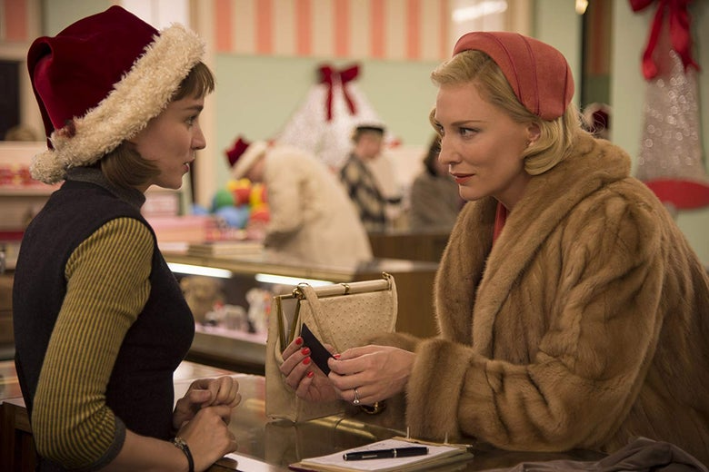 Rooney Mara wearing a Santa hat, in conversation with a fur-clad Cate Blanchett, who leans over a store counter.