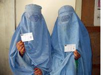 Women in burqas hold up their voter registration cards