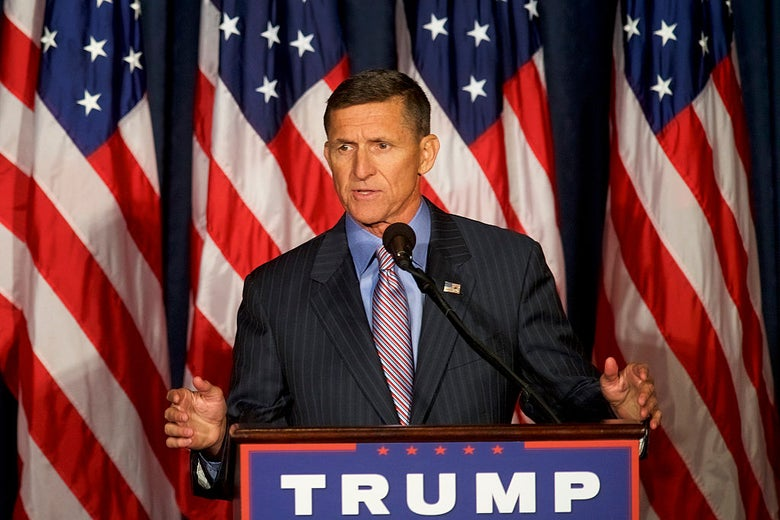 Flynn, wearing a pinstriped suit, speaks from behind a TRUMP logo on a lectern and in front of a row of American flags.