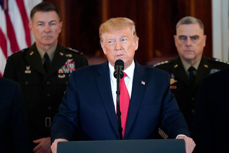 Donald Trump speaks at a podium, flanked by military officials.