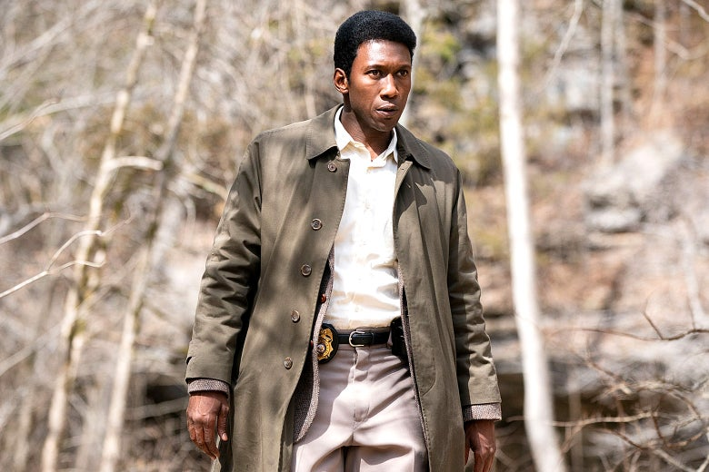 Mahershala Ali as Detective Wayne Hays, wearing a trenchcoat and walking in the woods.