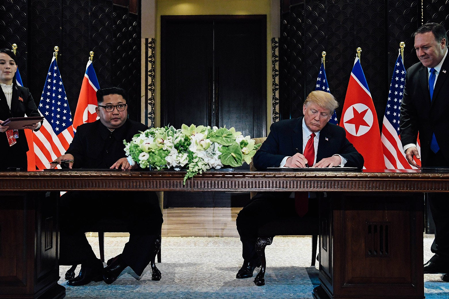 Kim Jong-un and Donald Trump seated at a large desk, signing documents.