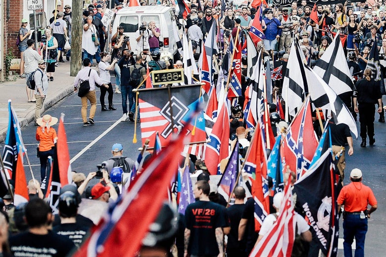 A group of white supremacists and other alt-right figures wave flags and march in Charlotesville.