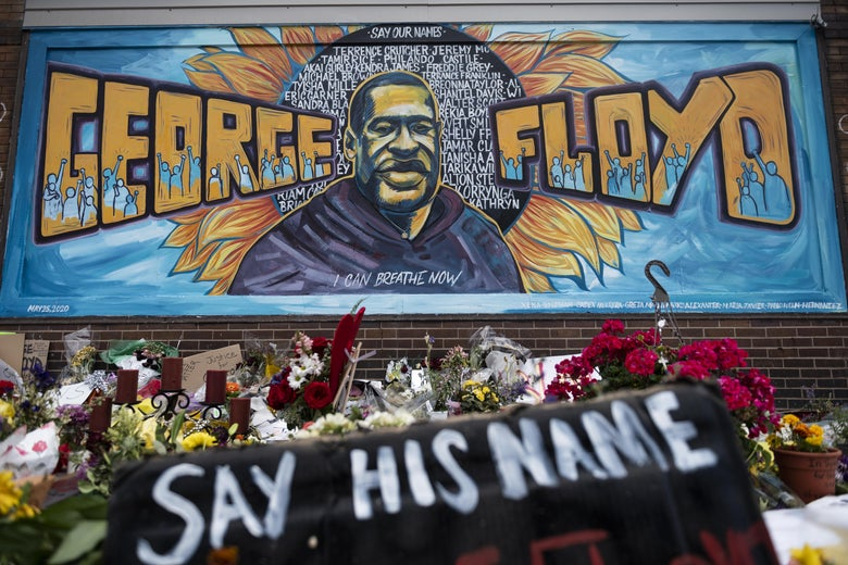 "A mural with George Floyd's face and name is seen. Flowers stand below it along with a spray-painted cloth that says ""Say His Name."""