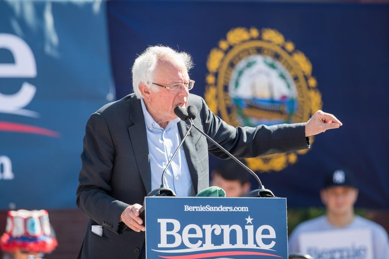 Bernie Sanders speaks from a podium at a political rally.
