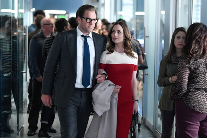 A man in a grey suit links arms with a brunette women in a red and black short-sleeve dress as they walk down a hallway.