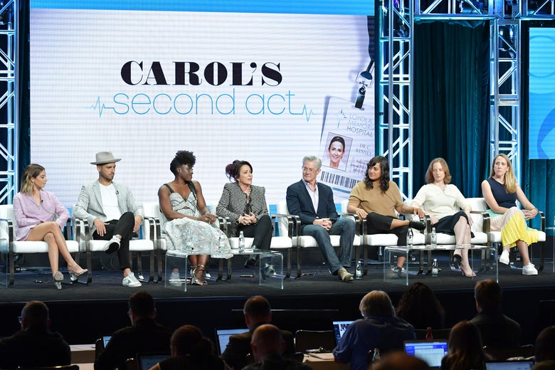 Actors Ashely Tisdale, Jean-Luc Bilodeau, Ito Aghayere, Patricia Heaton, Kyle MacLachlan, Sabrina Jalees, and showrunners Emily Halpern and Sarah Haskins of Carol's Second Act sit in a row on stage.