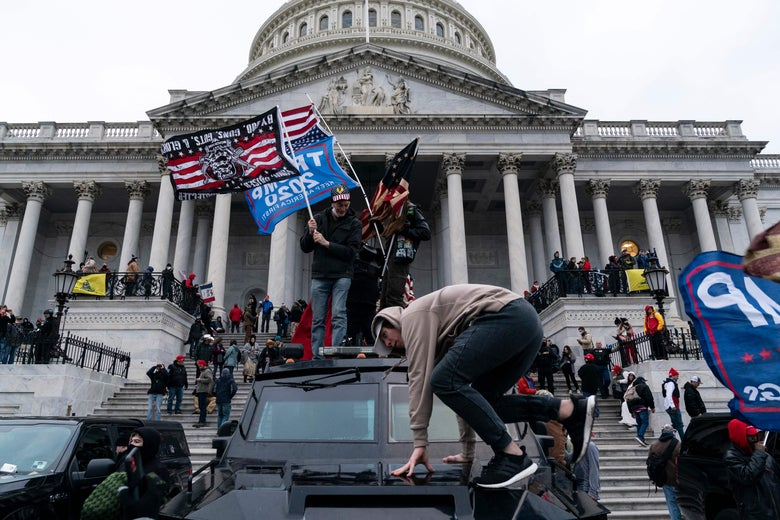 "A man jumps on a vehicle in front of the Capitol. Others stand on top of it, waving large ""Trump 2020"" flags. More protesters are massed on the Capitol steps."