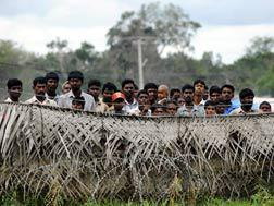 Sri Lankan war-displaced civilians peer from behind barbed wire fences. Click image to expand.