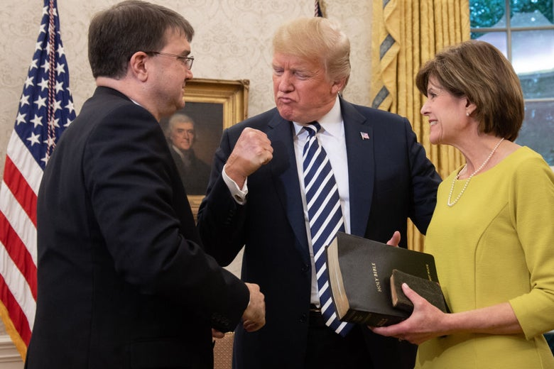 Trump, who is between Wilkie and his wife, pumps his fist.