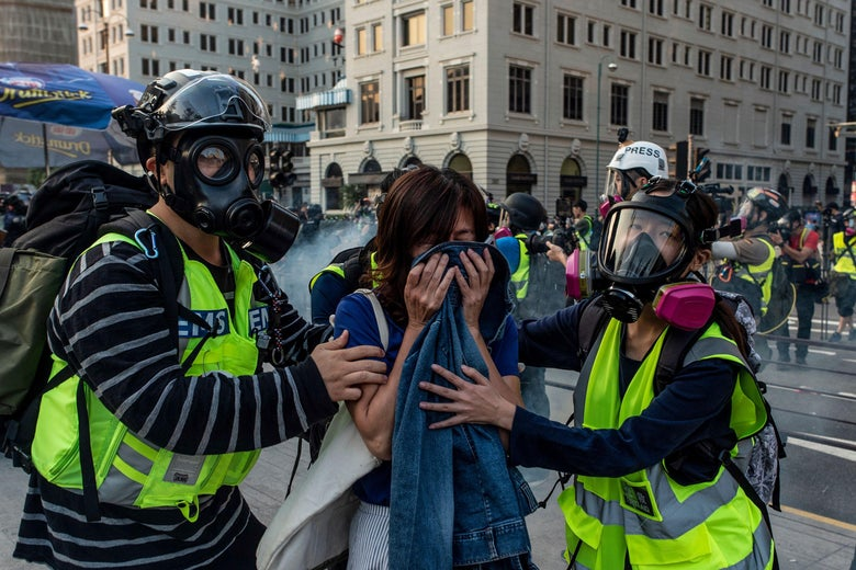First aid volunteers help a woman affected by tear gas during a march from the Tsim Sha Tsui district to Hung Hom in Hong Kong on December 1, 2019.