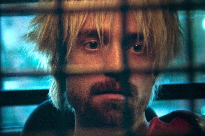 Robert Pattison, with blonde hair, stares from behind a grate.