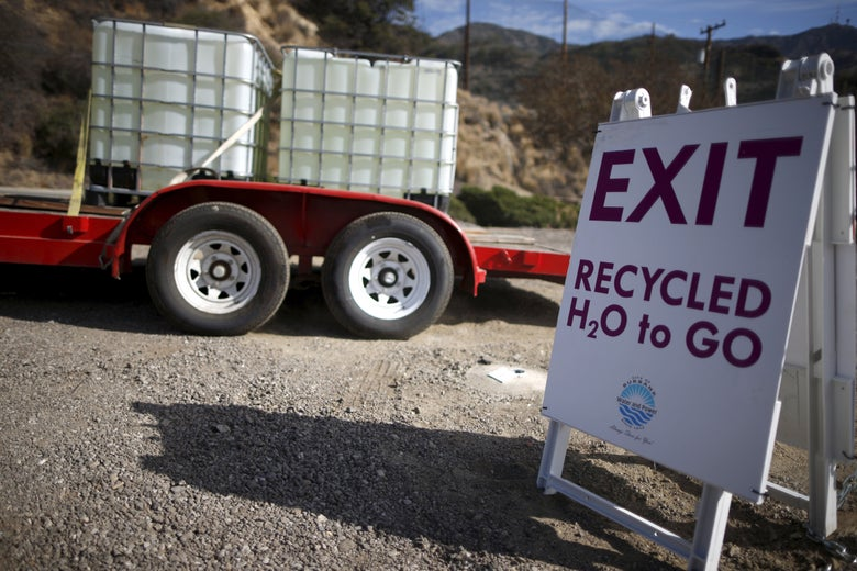 """A truck carrying tanks of water is seen behind a sign reading """"Exit. Recycled H2O to Go."""""""