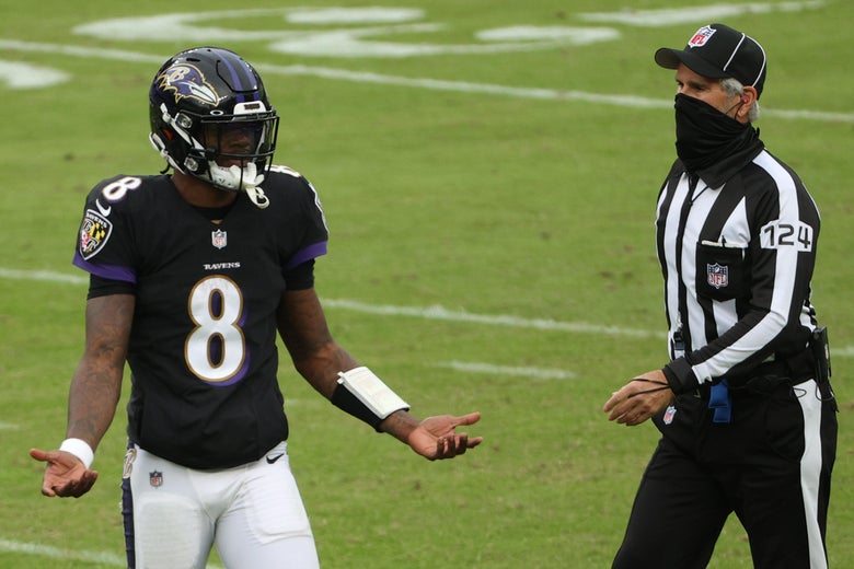 "Lamar Jackson in his Ravens uniform during a game with his hands out, like, ""wtf just happened?"" next to a referee with a mask on."