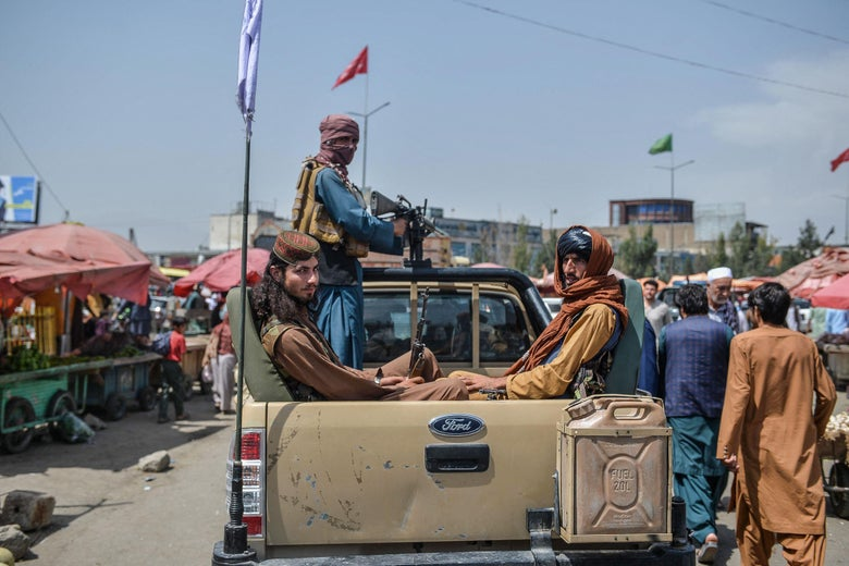 Taliban fighters ride in the back of a pickup truck through a crowded market area
