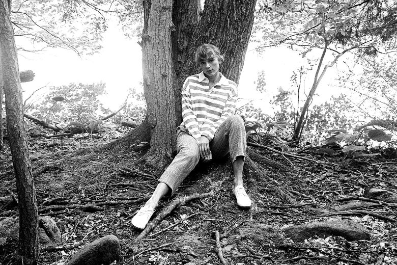 Taylor Swift sits on the ground in front of a tree.