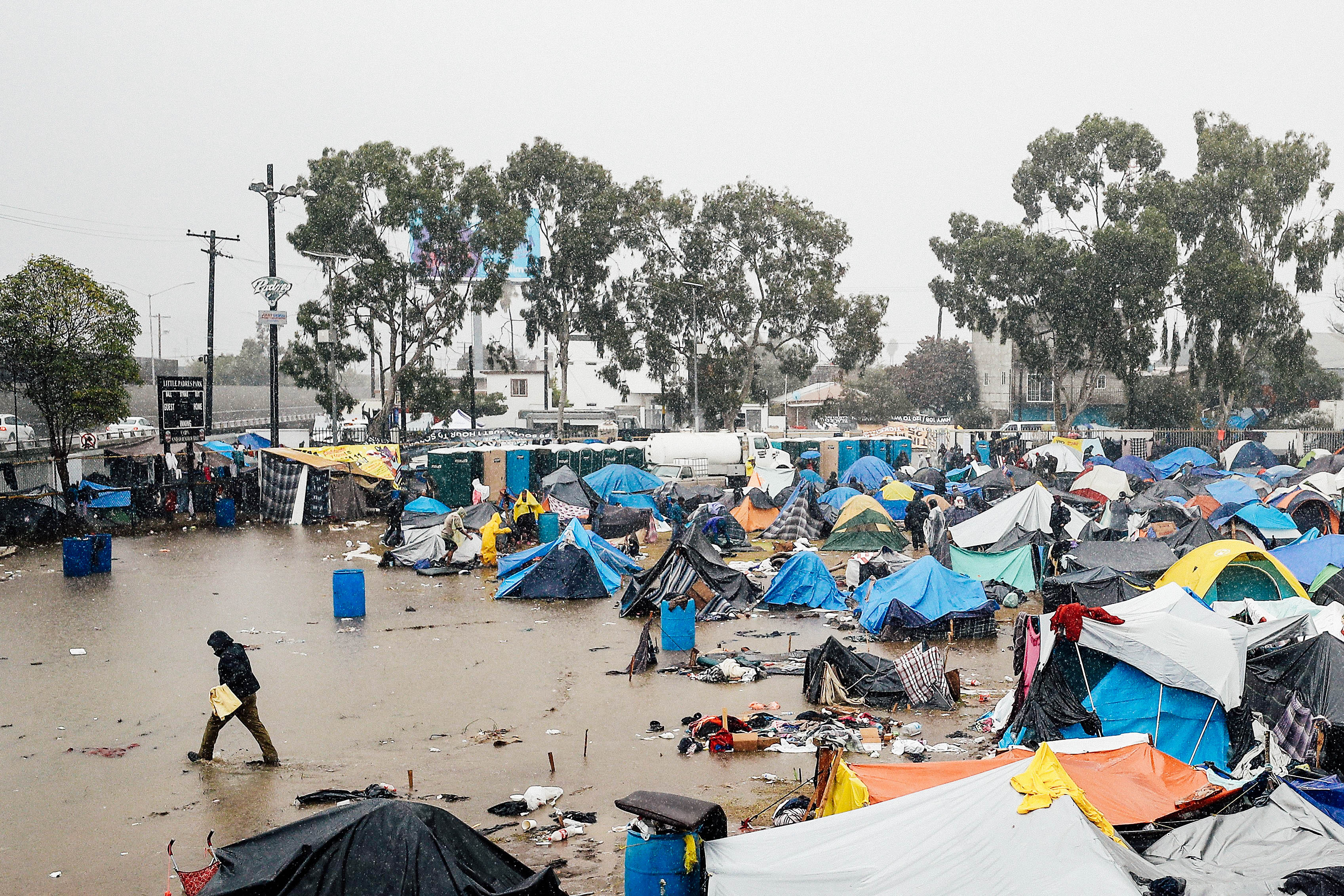 A person walks through a tent encampment flooded by rain.
