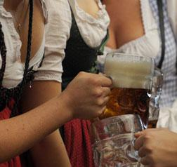 Girls in traditional Bavarian dirndls celebrate with beer in a Oktoberfest festival.