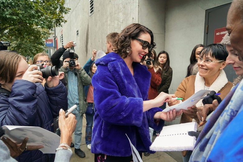 Katherine Heigl as her character in Firefly Lane in a blue coat signing autographs.