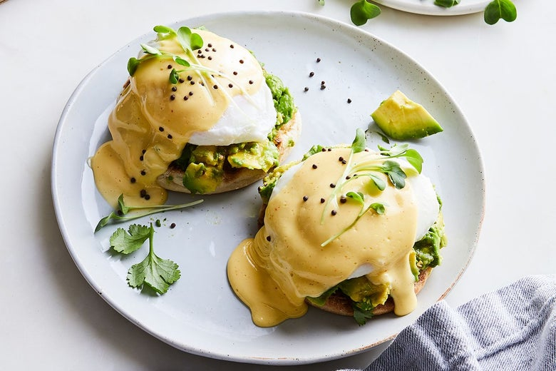 Two English muffins topped with avocado, poached eggs, and Hollandaise sauce