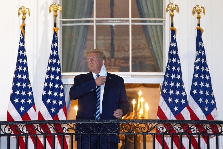 Donald Trump removes his mask while standing on a balcony with U.S. flags