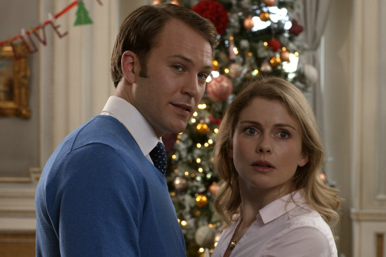 Ben Lamb and Rose McIver in a production still from the Netflix movie A Christmas Prince: The Royal Wedding. They stand facing each other in front of a Christmas tree.
