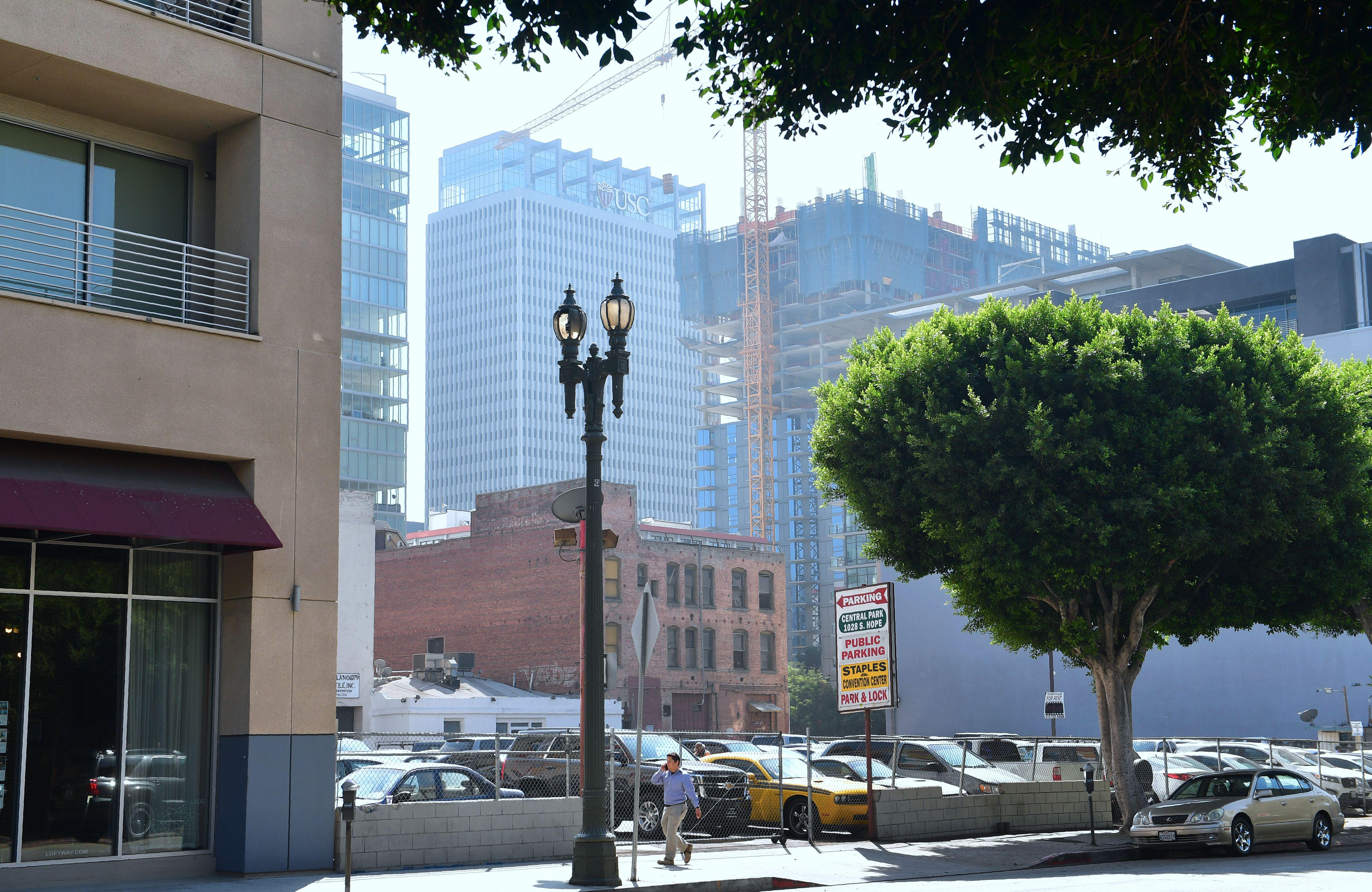 A pedestrian is dwarfed by new high-rise developments in downtown Los Angeles.