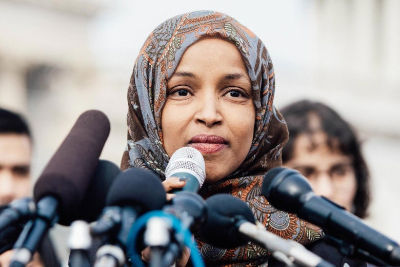Ilhan Omar with microphones in front of her.