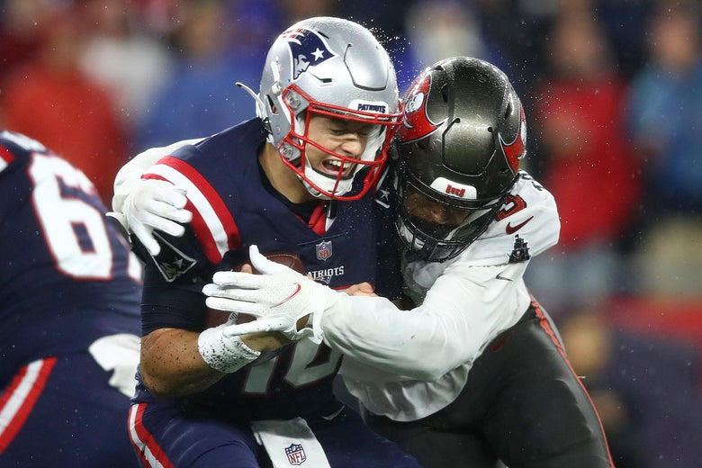 Tryon-Shoyinka wraps his arms around Jones, who holds the ball and grimaces with his eyes closed