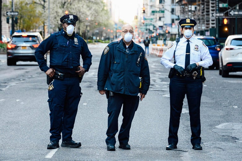 Three police officers blocking a road in NYC.