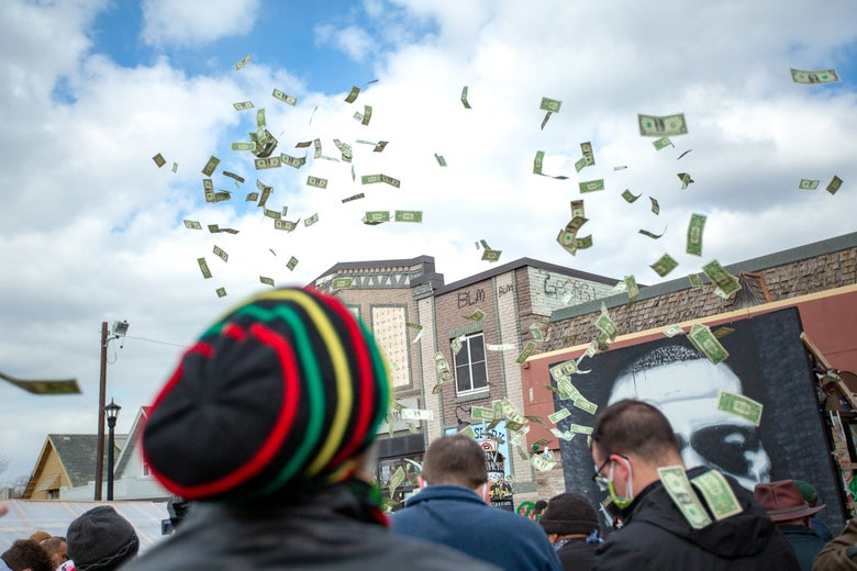 Cash flies in the air above George Floyd Square.