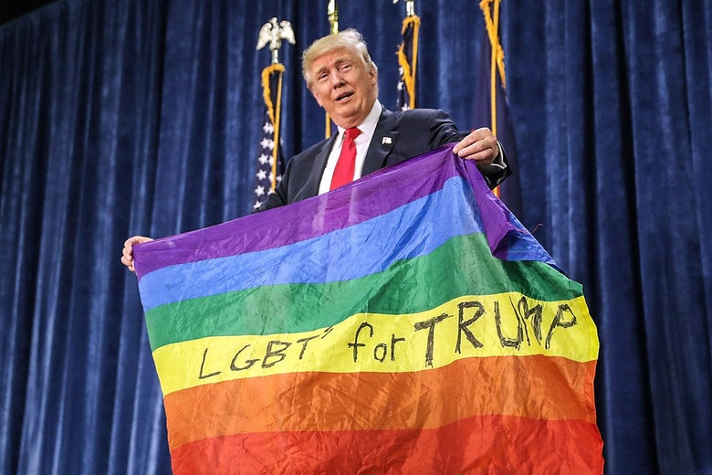 """Donald Trump holds up a rainbow flag with the words """"LGBTs for Trump"""" handwritten in the yellow stripe."""